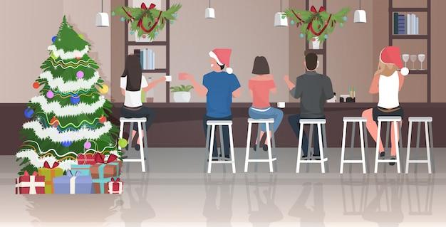 Menschen in weihnachtsmützen sitzen auf hockern im café und feiern weihnachten