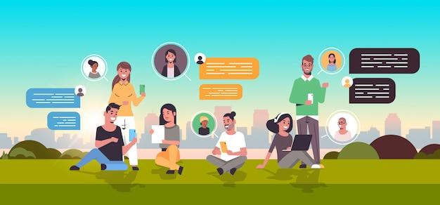 Menschen sitzen auf gras mit chat-app auf digitalen geräten social network chat-blase kommunikationskonzept