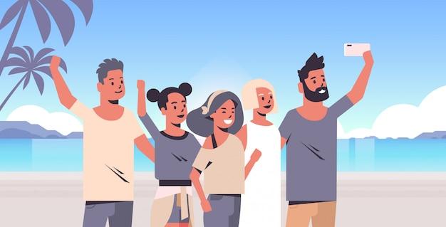 Menschengruppe am strand, die selfie-foto auf smartphone-kamera macht sommerferienkonzeptfreunde, die zusammen tropische insel-see-seeferien-ozeanreiseporträt horizontal stehen