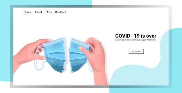 Menschliche hände, die medizinische maske auseinander reißen covid-19 ist über das ende des coronavirus-pandemie-quarantäne-konzepts hinaus