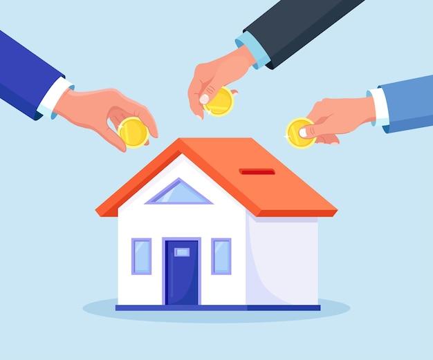 Menschliche hände, die münzen ins haus legen, ist wie ein sparschwein. winzige leute kaufen verschuldet ein haus. menschen investieren geld in immobilien. hypothekendarlehen, eigentum und ersparnisse. immobilieninvestition, hauskauf