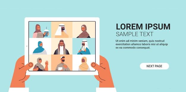 Menschliche hände, die tablet-pc verwenden, der mit arabischen freunden während des videoanrufs arabische leute unterhält, die virtuelle live-konferenzkommunikationskonzept horizontale kopienraumillustration haben