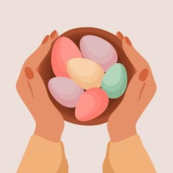 Menschliche hände halten osterkorb mit verzierten eiern draufsicht. bunte schokoladeneier.