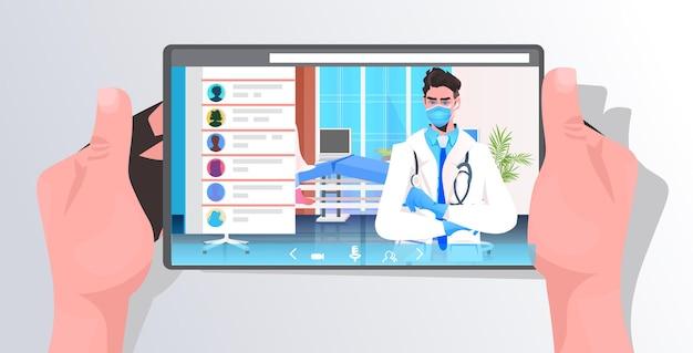 Menschliche hände mit tablette mit männlichem dotor auf dem bildschirm online-beratung covid-19-pandemie-konzept