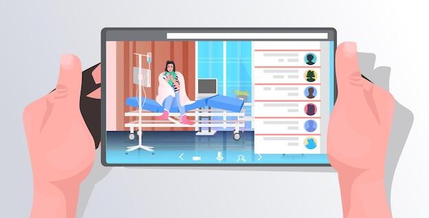 Menschliche hände unter verwendung einer tablette mit einer kranken patientin auf dem bildschirm covid-19-pandemiekonzept