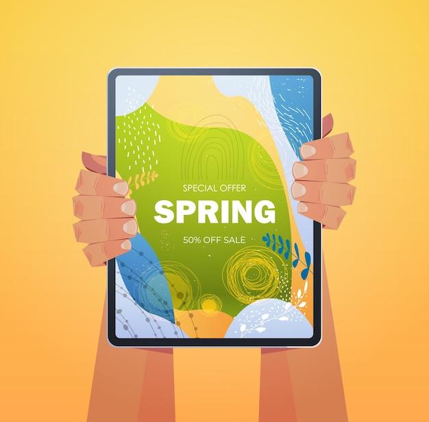 Menschliche hände unter verwendung tablet-pc mit spring sale banner flyer oder grußkarte auf bildschirm vertikale illustration