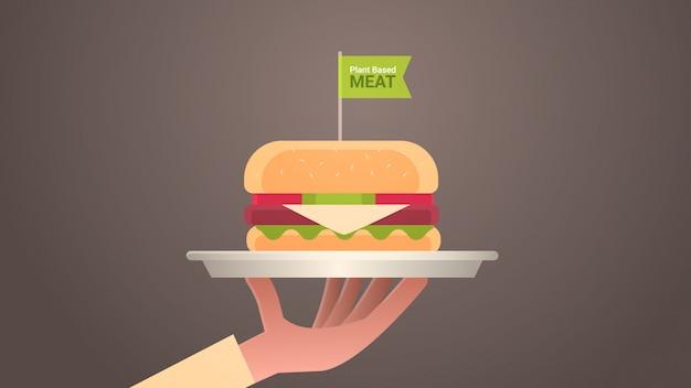 Menschliche hand, die pflanze basierend auf fleischhamburger mit vegetarischem lebensmittelkonzept der veganen flagge des gesunden lebensstils horizontal hält