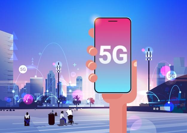 Menschliche hand hält smartphone 5g online-kommunikationsnetzwerk drahtlose systeme verbindungskonzept