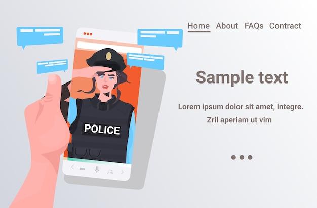 Menschliche hand unter verwendung des smartphones, das mit der polizistin während der online-kommunikation des videoanrufs chattet