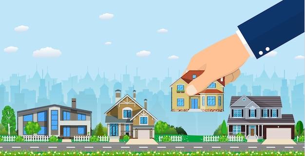 Menschliche hand wählt aus, um ein rechtes haus zu halten. immobilien zum verkauf, immobilien.