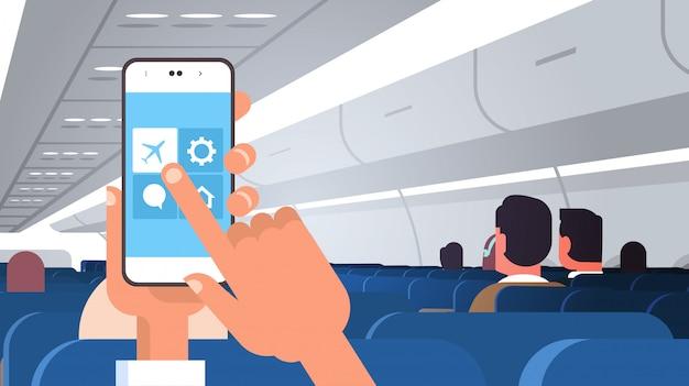 Menschliches händchen haltendes smartphone mit flugmodusregeln des modernen flugzeugbretts des flugzeugsicherheitskonzepts mit horizontaler ebene der passagiere