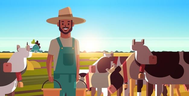 Milchmann, der eimer mit frischem milchbauer hält, der nahe herde von kühen steht, die auf grasfeld weiden