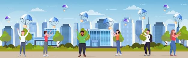 Mischen sie leute, die paketboxen fangen, die mit fallschirm vom himmel transportversandpaket luftpost-expressversandkonzept fallen, moderner stadtbildhintergrund in voller länge horizontal