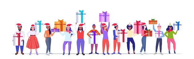 Mischen sie rassenleute in weihnachtsmannhüten, die geschenkgeschenkboxen halten frohe weihnachten frohes neues jahr winterferien feiern