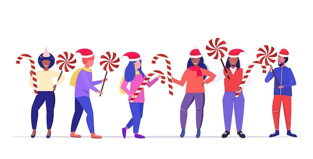 Mischen sie rassenleute in weihnachtsmannhüten, die süßigkeiten halten, die zuckerstange und lutscher frohe weihnachten frohes neues jahr winterferienfeier halten