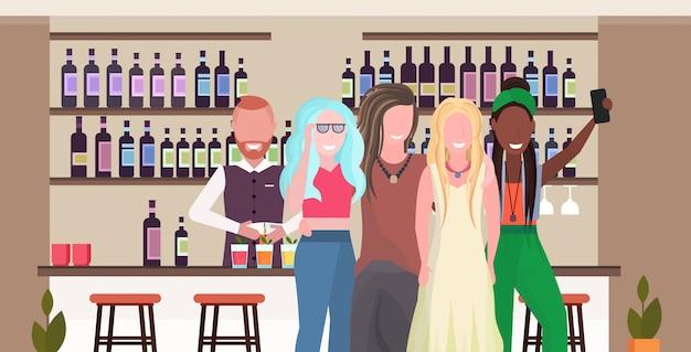 Mischen sie rassenmädchen, die selfie-foto auf smartphone-kamera-leuten machen, die sich in der bar entspannen, die cocktails trinkt barmann, der kunden modernes café-innenhorizontalporträt dient