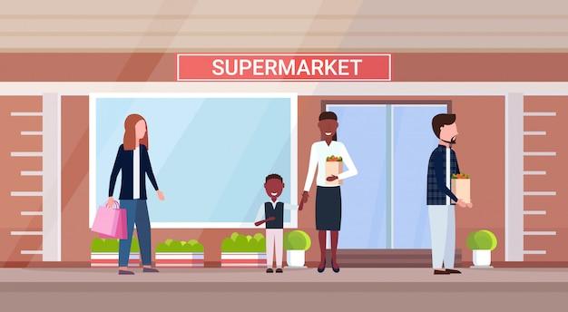 Mischen sie rassenmenschen beim halten von einkaufstüten mit lebensmittel-comicfiguren, die im freien modernes lebensmittelgeschäft supermarkt außen horizontal stehen