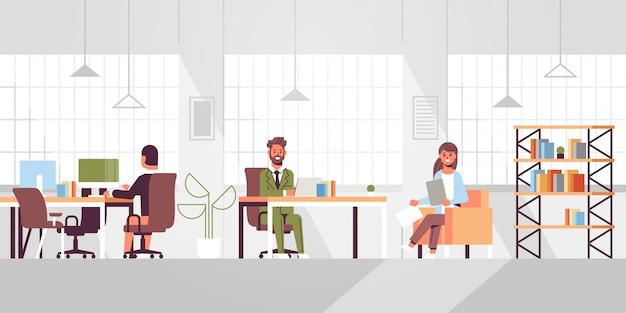 Mitarbeiter des unternehmens mitarbeiter, die in kreativen, kooperierenden open space-mitarbeitern arbeiten geschäftsleute, die am arbeitsplatz sitzen und über das neue büro des neuen büros für neue büroräume diskutieren