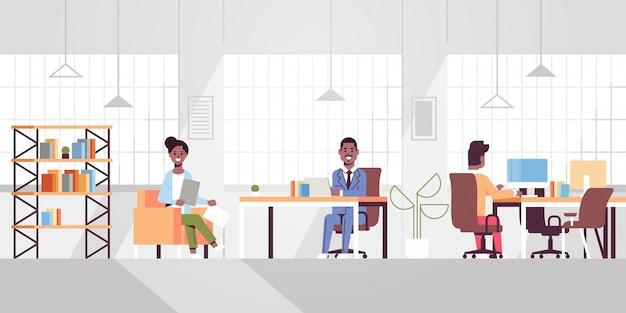 Mitarbeiter des unternehmens mitarbeiter, die in kreativen, zusammenarbeitenden open space-geschäftsleuten arbeiten, die am arbeitsplatz sitzen und über ein neues projekt diskutieren