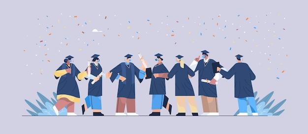 Mix-race-absolventen in masken stehen zusammen glückliche absolventen, die das akademische diplom feiern