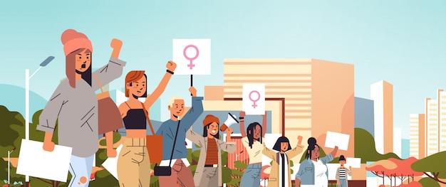 Mix race aktivisten halten plakate mit weiblichem geschlecht zeichen feministische demonstration mädchen macht bewegung rechte schutz frauen empowerment konzept porträt stadtbild hintergrund horizontal