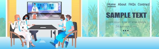 Mix race doctors team mit virtuellen konferenzspezialisten in masken, die während eines videoanrufs diskutieren