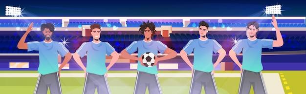 Mix race footbal-spieler, die zusammen auf der stadionfußballmannschaft stehen und bereit sind, das horizontale porträt des spiels zu starten