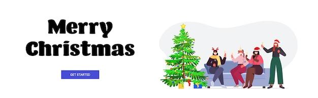 Mix race freundinnen in santa hüte und masken trinken champagner neujahr weihnachten feiertage feier konzept in voller länge schriftzug gruß banner