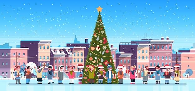 Mix race kinder gruppe in der nähe von geschmückten tannenbaum stadt gebäude häuser winter street