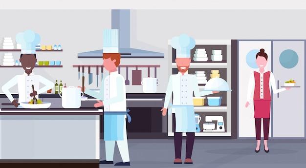 Mix race köche kochen essen kulinarisches personal teamwork-konzept moderne kommerzielle restaurant küche innen horizontale wohnung