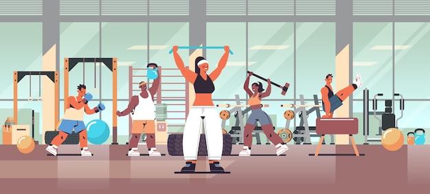 Mix race menschen, die körperliche übungen machen, trainieren fitness-training gesunden lebensstil konzept modernen fitnessstudio studio interieur