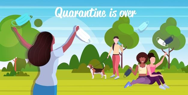 Mix race menschen, die masken abnehmen und im park im freien spazieren gehen, um die coronavirus-quarantäne zu feiern, endet