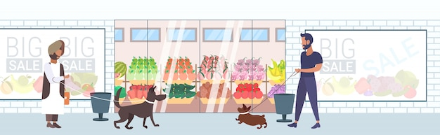 Mix race menschen, die mit hunden spazieren gehen und spaß vor dem supermarkt-einkaufszentrum haben