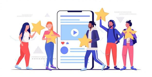 Mix race menschen halten bewertung sterne kunden bewertung kundenfeedback zufriedenheitsgrad konzept männer frauen mit online-mobilanwendung skizze in voller länge horizontal