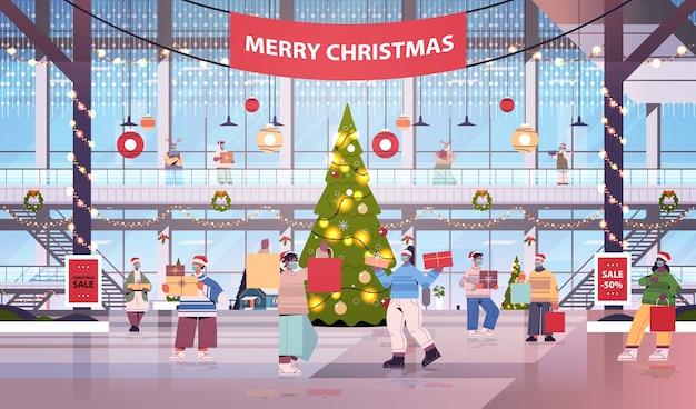 Mix race menschen zu fuß mit einkäufen in einkaufszentrum dekoriert für frohe weihnachten und neujahr winterferien feier großen laden interieur horizontale vektor-illustration in voller länge