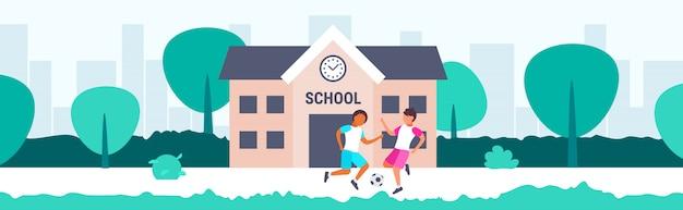 Mix race schüler spielen fußball vor dem schulgebäude grundschulkinder, die spaß haben zurück zum schulkonzept stadtbild hintergrund in voller länge horizontal