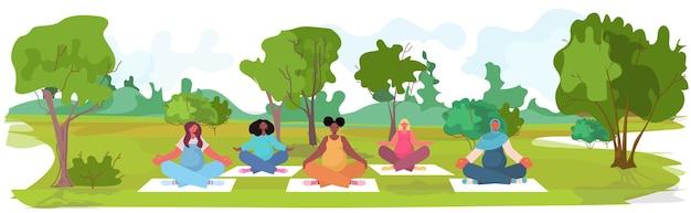 Mix race schwangere frauen, die yoga fitnessübungen trainieren, trainieren gesunde lebensstil konzept mädchen, die im parklandschaftshintergrund meditieren