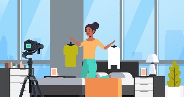 Mode-blogger hält kleiderbügel mit kleidung afroamerikaner frau aufnahme online-video live-streaming social-media-blogging-konzept modernes schlafzimmer innenporträt horizontal
