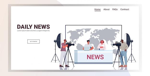 Moderatoren, die mit kameraleuten im fernsehen senden und über tägliche nachrichten im modernen fernsehstudio diskutieren