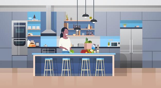 Moderner kithcen innenraum und junge afroamerikaner-frau, die salat kocht
