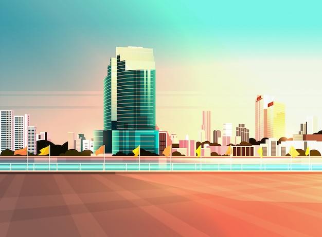 Moderner wolkenkratzerzaun und fluss gegen stadtbildsonnenuntergang