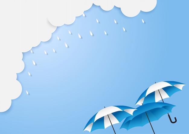 Monsun, regenzeithintergrund mit copyspace. wolkenregen und -regenschirm auf blauem himmel.