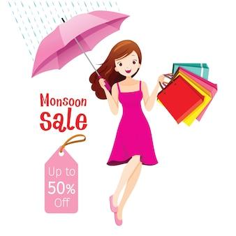 Monsun-verkauf, frau unter regenschirm, der mit vielen einkaufstaschen springt