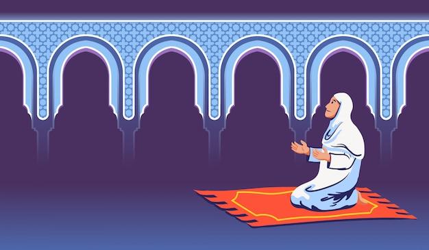 Moslemische frau sitzen und beten nahe dekorativem moscheentor.