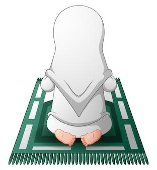 Moslemische frauen, die auf dem gebetsteppich beim beten sitzen