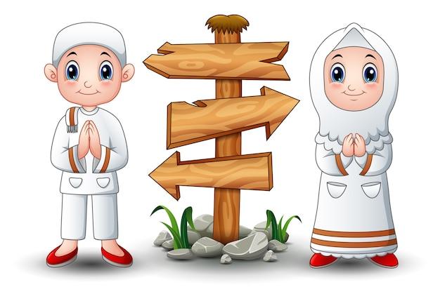 Moslemische kinderkarikatur mit leerem hölzernem pfeilzeichen