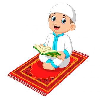 Moslemischer junge, der heiligen quran liest