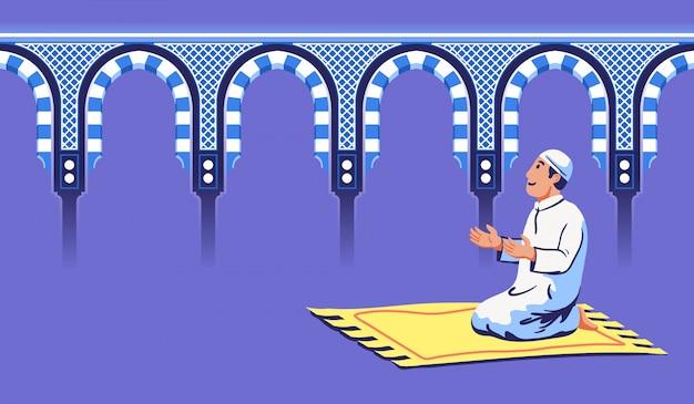 Moslemischer mann sitzen und beten nahe dekorativem moscheentor.