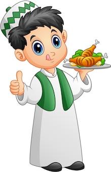 Moslemisches kind, das eine servierplatte des hühnerfleisches hält und daumen aufgibt