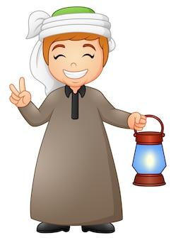 Moslemisches kind, das zwei finger mit dem halten von laterne gibt